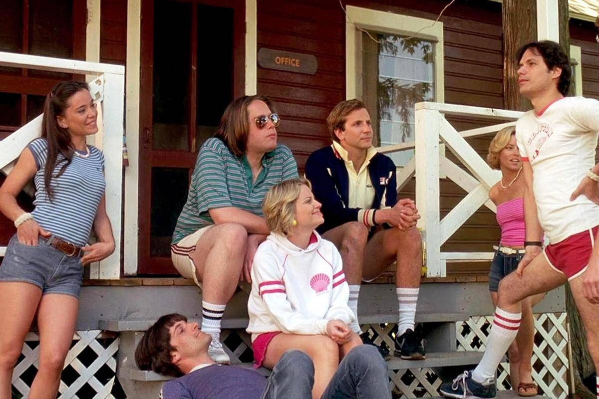 cast of wet hot american summer sitting in front of a cabin
