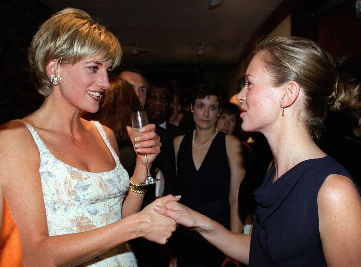 While wearing a low-cut dress by Catherine Walker, Diana shakes hands with supermodel Kate Moss.