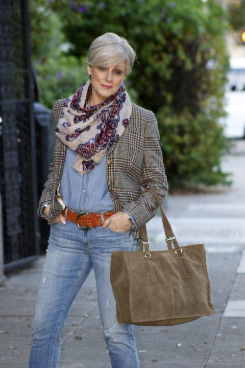 An older woman wears a jacket and scarf in creative patterns.